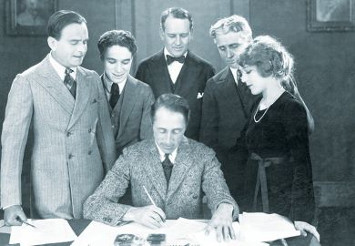 Filmmaker D. W. Griffith reviews the contract of Mary Pickford, accompanied by (l-r) her husband, Douglas Fairbanks, and Charlie Chaplin, and their two attorneys. Illustrating jump in teaching contracts under REF