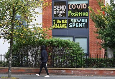 A man walks past messages pasted inside the windows of student accommodation at Manchester Metropolitan University
