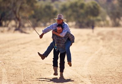 Cowboy carries friend on his back