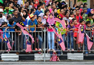 Crowd of people waving Malaysian flags