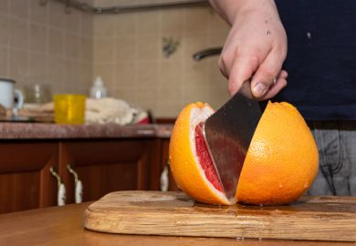 Cutting a grapefruit with a kitchen hatchet on a wood board