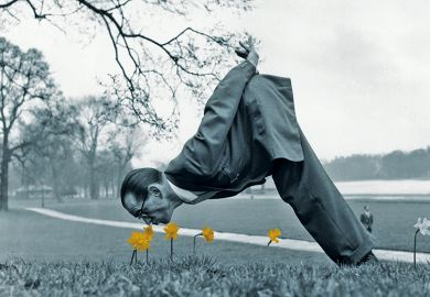 Man dressed in vintage suit sniffing daffodils