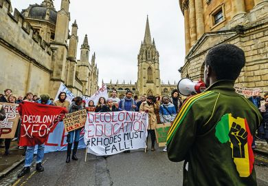 A student in an African-style jumper speaks to demonstrators outside University of Oxford's All Souls College