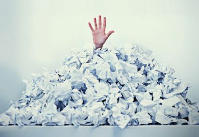 Hand sticking out of a mound of crumpled paper