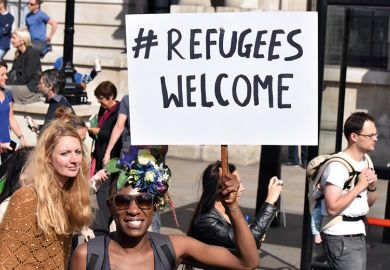 Demonstrator holding 'Refugees welcome' placard, London, England