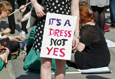 Demonstrator wearing 'It's a dress, not yes' placard