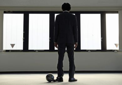 Depressed businessman with ball and chain around ankle