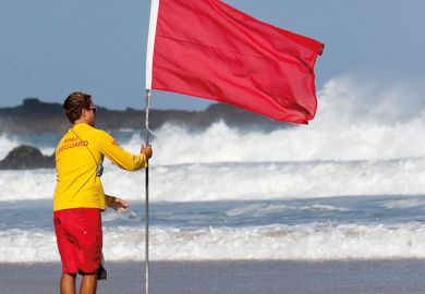 Man holding red flag on beach