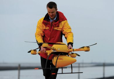 DHL employee prepares PaketKopter drone for delivery