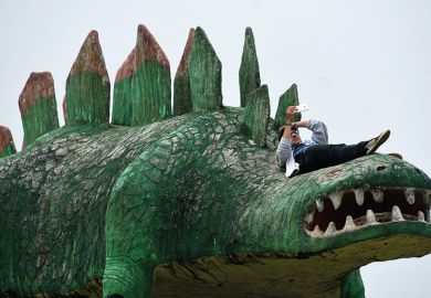 Man on dinosaur sculpture