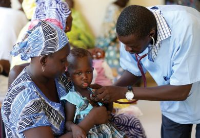 Doctor examining young child patient, Dakar, Senegal