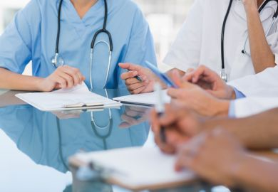 Doctors in a meeting symbolising disagreements about healthcare education