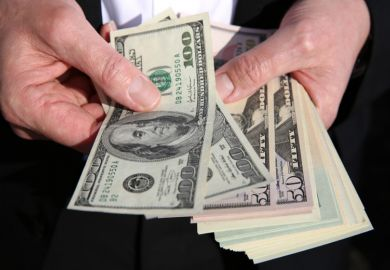 US dollars in a man's hand
