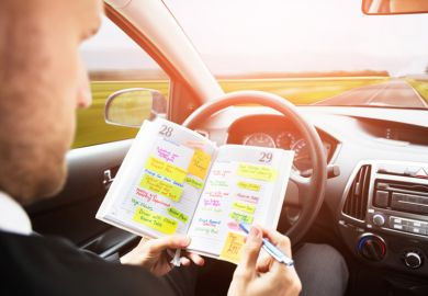 A man looking through his diary in a driverless car