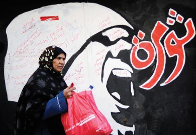 Egyptian woman walks past 'Revolution' graffiti, American University in Cairo
