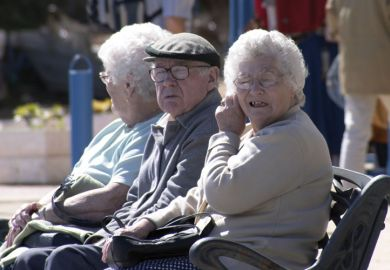 Elderly man and women sitting on bench