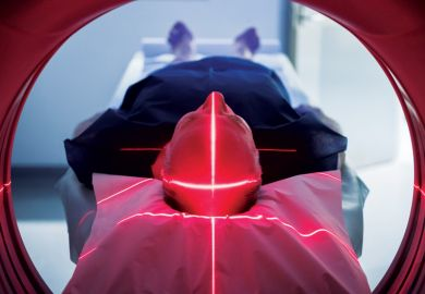 Elderly man lying down in Body CT (CAT Scan) machine
