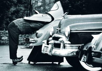 man looks under car bonnet