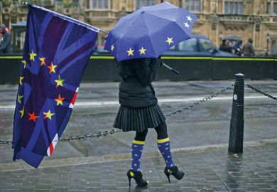 Person holds Union Jack and European Union flag and umbrella