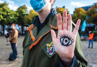 XR activists standing up with eyes painted on placards in front of the House of the Parliament where the New Extinction Rebellion campaign has started in The Hague, Netherlands on September 1, 2020
