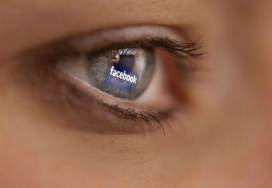 Reflection of Facebook logo on person's eye