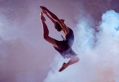 Female ballet dancer jumping through dry ice