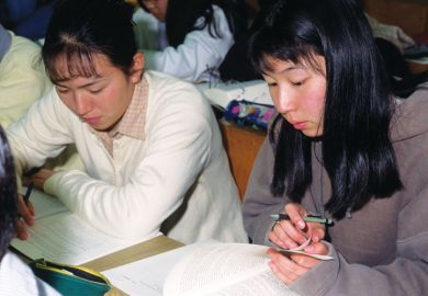 Female Japanese students reading textbooks