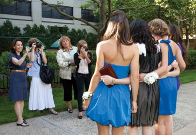 Female students being photographed by their mothers and sister before senior prom