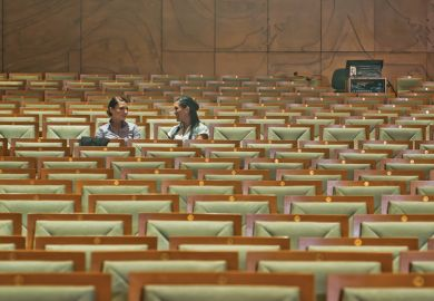 Female students chatting in empty lecture hall
