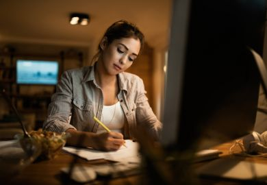 Female student taking notes while learning at night at home