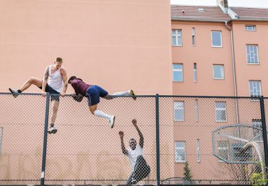 Men climbing over fence