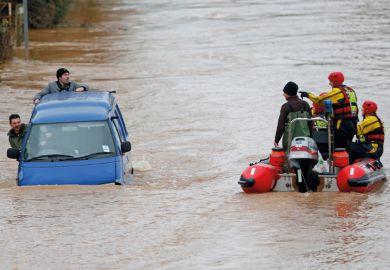 Firemen rescuing men in sinking van, Gloucester, England, 2012