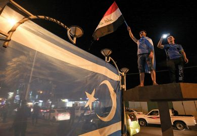 Iraqis wave their national flag and the flag of the Iraqi Turkmen as they celebrate in the city of Kirkuk in October 2017