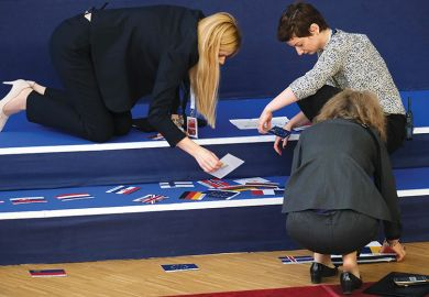 Workers sort flags to mark the spots where European leaders will stand for the family photo during EU summit on March 22, 2019 in Brussels, Belgium