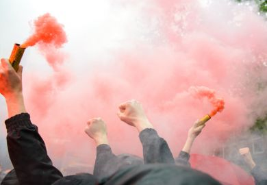 Dutch football fans clench fists and hold orange flares