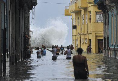 Cubans wade through a flooded street in Havana after Hurricane Irma swept through the country in 2017