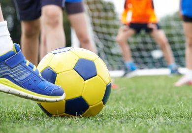 Football player kicking ball towards goal