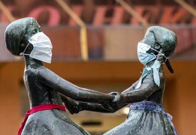 The two female heads of a bronze figure wear a protective face mask on April 3, 2020 in Jena, Germany