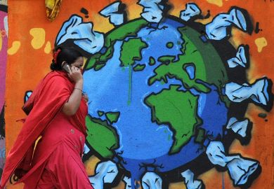 A woman on a phone walks past a graffiti depicting world map affected with Coronavirus. India.