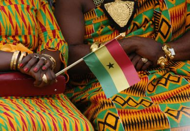 Women in kente dresses with Ghana flag
