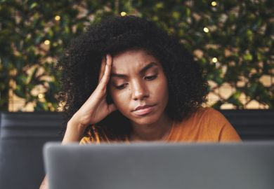 A sad young woman looks at a laptop