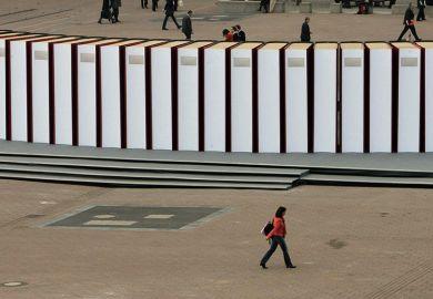 Visitors walk past giant books at the Frankfurt Book Fair. Germany