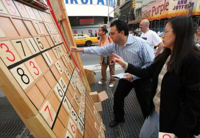 Jim Ressler, owner of Sudoku Board USA, helps Dorris Lam of Glen Rock, N.J., solve a Sudoku puzzle on a gigantic board in Times Square