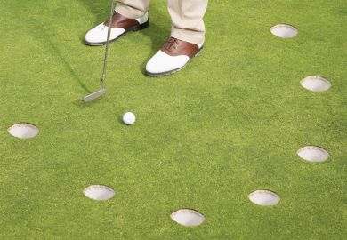 Golfer putting on green with multiple holes
