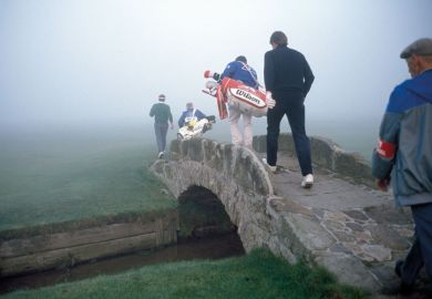 Golfers crossing a bridge in fog