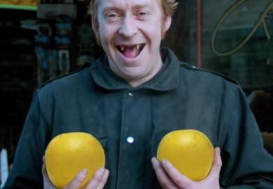 Man holding pair of grapefruit