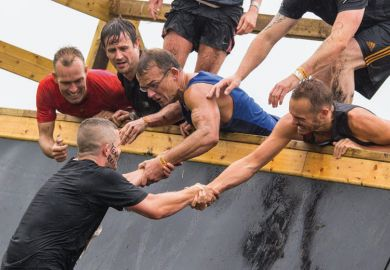 Group of men assisting teammate on obstacle course