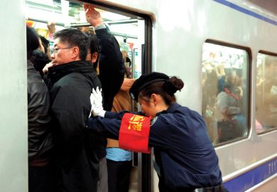 Guard pushes people onto train in Beijing