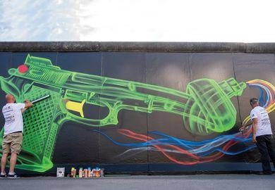 """Street artists create an updated likeness of Swedish artist Carl Fredrik Reuterswaerd's famous """"Knotted Gun"""" sculpture on a segment of the former Berlin Wall, 2020"""