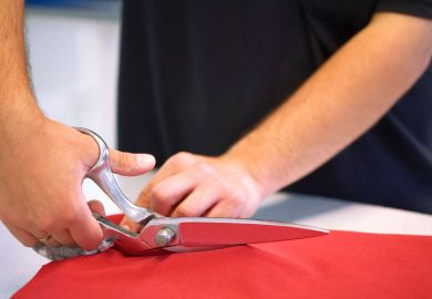 Hand cutting red cloth with scissors